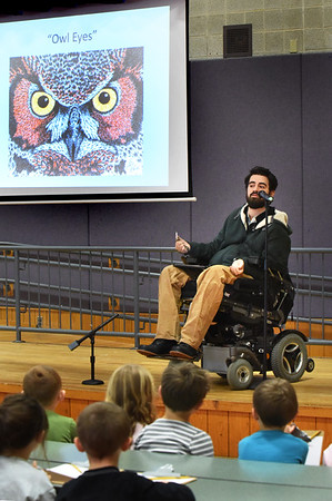 BRYAN EATON/Staff photo. Artist Nathaniel Bibaud shows some of his work to students at Amesbury's Cashman Elementary School on Tuesday morning. He's a former student of the Amesbury School system and was   presenting his journey as an artist and the challenges he faced when an accident changed his life when he was paralyzed in a car crash while living in St. Croix and how he used art to move forward.