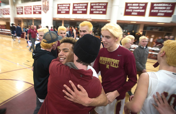 JIM VAIKNORAS/Staff photo Newburyport's George Coryell is congratulated by classmates and teammate after his last second steal and basket against Swampscott at Newburyport High School Monday night.