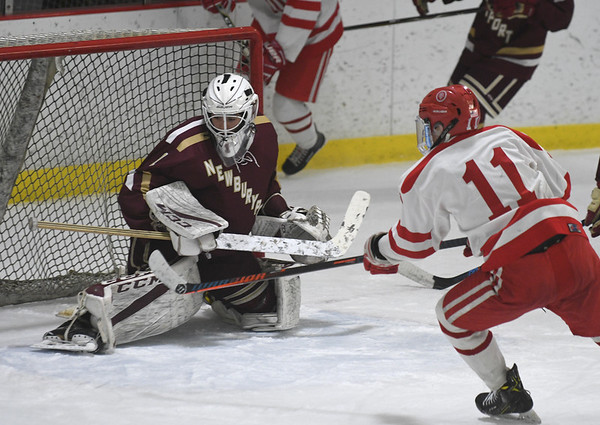 JIM VAIKNORAS/Staff photo Newburyport's Jackson Marshall makes a stop on St John's Matthew Myers during their game at the Graf Rink in Newburyport Friday.