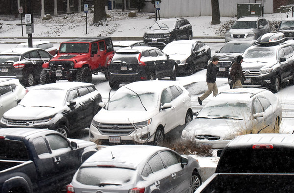 BRYAN EATON/Staff photo. People parked in Newburyport's Green Street Parking Lot needed little more than windshield wipers and brush to clean their cars if they left before dark as there was only a heavy dusting of snow. The accumulation was supposed to turn to rain overnight with the weather system out by around 7:00 a.m.