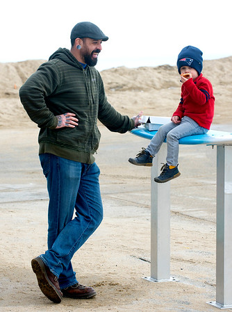 JIM VAIKNORAS/Staff photo Cohle Pilla, 3, of Amesbury enjoys the warm weather and a piece of pizza with his dad Steve on Salisbury Beach Monday.