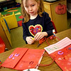 BRYAN EATON/Staff photo. Wearing a heart on her shirt, fittingly, Caroline Courtney, 6, decorates her Valentine bag. She was in Kathy Armstrong's class at Amesbury Elementary School getting ready for their party on Thursday.