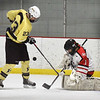 BRYAN EATON/Staff photo. Amesbury goalie Charlie Baxter deflects the puck on a shot by Haverhill's Hayden Flaherty.