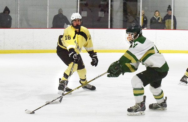 BRYAN EATON/Staff photo. Pentucket's Jack Queenan harnesses the puck as Haverhill's Mike Fitzgerald covers.
