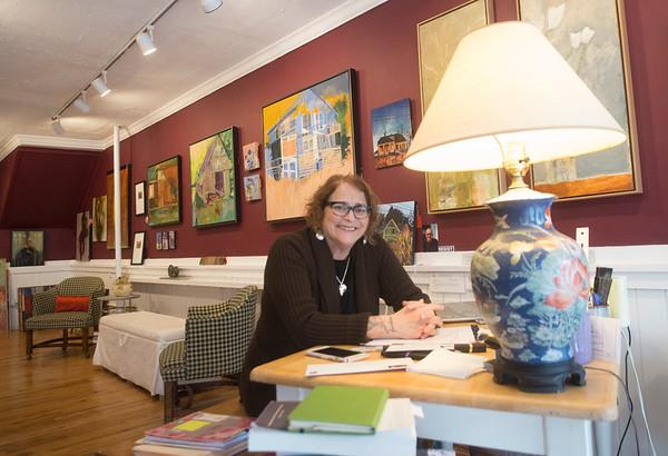 JIM VAIKNORAS/Staff photo Paula Estey sits at her desk at her Harris Street Gallery in Newburyport.