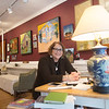 JIM VAIKNORAS/Staff photo Paula Estey sits at her desk at her Harris Street Gallery in Newburyport.