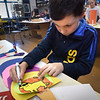 BRYAN EATON/Staff photo. Camden Walton colors in a lion on the bottom of an ice cream cone he created in Karen Greenfields art class at the Cashman School in Amesbury. Students were working on different projects including them using their own creative expressions of ideas.