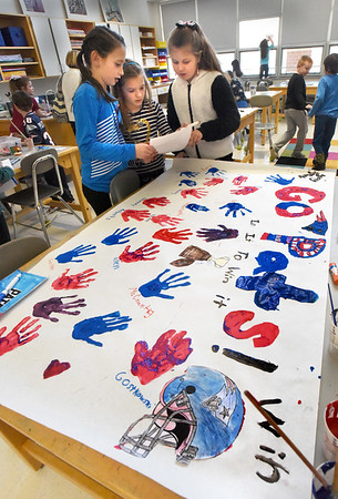 BRYAN EATON/Staff photo. From left, Summer Pawlick, Brooke Baumann and Olivia Eaton, all 10, look over the Patriots' starting roster to write each players name under handprints for a mural they're making hoping for a Superbowl win. They were in Salisbury Elementary School's afterschool program Explorations of Colors and Painting.