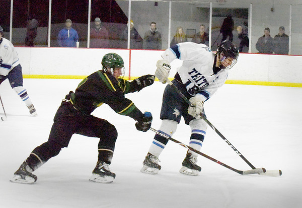 BRYAN EATON/Staff photo. Pentucket's RIchie Hardy and Triton's Sammy Rennick battle for the puck.