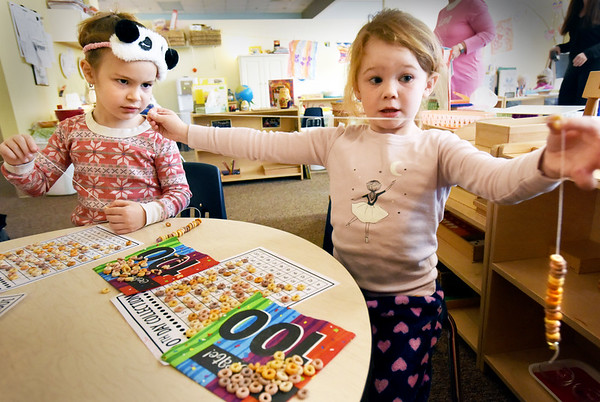 BRYAN EATON/Staff photo. Eliza Kopp, 5, left, and Kenzie Eiserman, 4, string the 100 Cheerios they counted out on a ten by ten grid at the Newburyport Montessori School. They were celebrating the 100th day of school wearing pajamas and eating pancakes after their project was completed.
