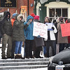 BRYAN EATON/Staff photo. A couple dozen people held signs waving to motorists in Newburyport's Market Square around lunchtime on Monday. They were protesting President Trump's declaration of an emergency over his proposed border wall with Mexico.