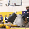 "JIM VAIKNORAS/Staff photo 	Newbury Elementary School principal Beth Yando rides a mechanical bull to the strains of Lynyrd Skynyrd ""Sweet Home Alabama"" in the school gym Wednesday. Yando surprised the students as a reward for the school raising over $23,000 for the PTA. Student were asked for suggestions for the reward and she picked one by second graders Kodi Koch and Evan Allen.  A number of teachers and staff members took a turn on the bull."