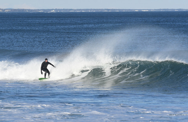 JIM VAIKNORAS/Staff photo A surfer takes advantage of the bright afternoon sunshine as he catches a wave at Salisbury Beach Friday afternoon.