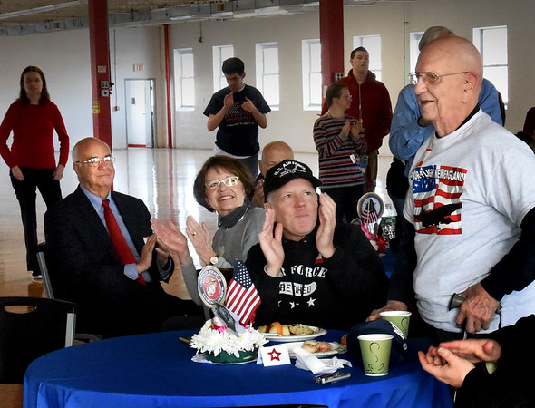 BRYAN EATON/Staff photo. World War II U.S. Navy veteran Herbert Erikson, right, was recognized with other veterans at Valentine's Day coffee hour at Coastal Connections in Amesbury on Thursday morning. Applauding from left, Amesbury Mayor Ken Gray and his wife, Donna, and Erikson's son, U.S. Air Force Brigadier General, and chaplain, Richard Erikson, Ret.
