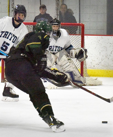 BRYAN EATON/Staff photo. Triton goalie Connor Beevers braces for a shot on net and makes the save.