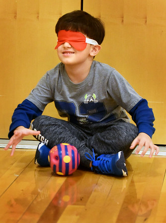 "BRYAN EATON/Staff photo. Kindergartner Arthur DiBenedetto, 5, tries to grab a ball making a sqeaking noise while blindfolded in physical education class at the Bresnahan School in Newburyport on Monday afternoon. They were at different stations learning how people with disabillities get by with daily tasks and how to help those people, if needed, and given an understanding of how people can cope and excel. The organization Northeast Passage, which empowers individuals with disabilities to ""Define, Pursue and Achieve,"" will be in the classes at the end of the week showing students how to manage physical activity while in a wheelchair."