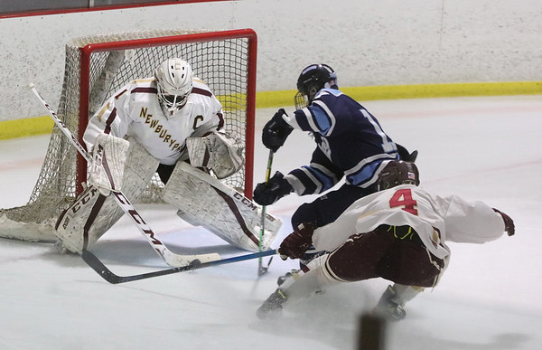 MIKE SPRINGER/Staff photo<br /> Newburyport goalie Jackson Marshall stops a shot from point-blank range by Ryan Lindholm of Triton as Marshall's teammate  Cam Caponigro moves in to clear the puck away during varsity hockey action Monday in Newburyport.