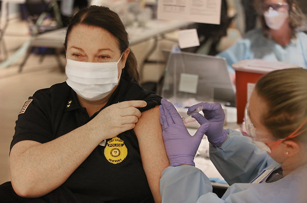MIKE SPRINGER/Staff photo<br /> Newbury Deputy Police Chief Patty Fisher holds still while Nelson Lane, school nurse at the Francis T. Bresnahan School, injects the Covid-19 vaccine in her arm during a vaccination clinic Thursday for area first responders at the Newburyport Senior/Community Center.