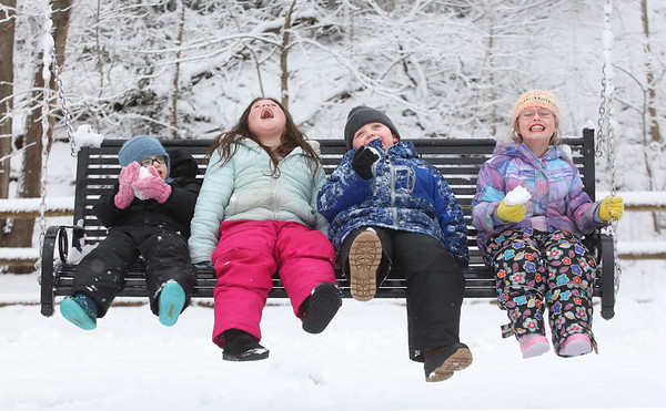 MIKE SPRINGER/Staff photo<br /> Friends, from left, Spencer Brown, 2, Ava Dobkowski, 5, Chance Laskiewicz, 4, and Riley Brown, 4, enjoy eating snow and relaxing on the swing together Thursday while taking a break from sledding at March's Hill in Newburyport.