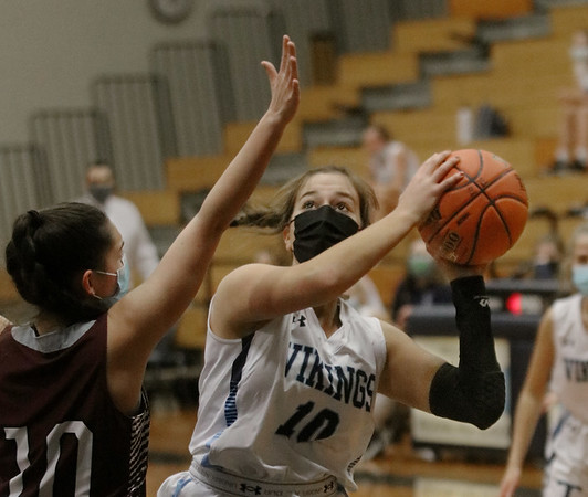 MIKE SPRINGER/Staff photo<br /> Triton's Olivia Kiricoples, right, goes up for a basket against Alexa Osier of Rockport during varsity basketball action Friday at Triton.