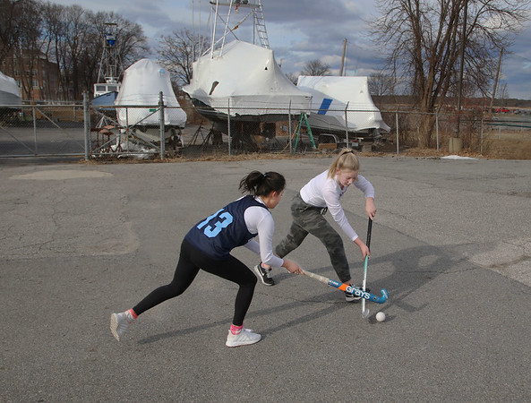MIKE SPRINGER/Staff photo<br /> Fourteen-year-old Ruby Field, right, teaches her friend Nora Geerlings, also 14, how to play field hockey after school Wednesday in Newburyport.