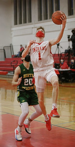 MIKE SPRINGER/Staff photo Amesbury's Camden Keliher goes up for a lay-up ahead of Andrew Boulas of North Reading during varsity basketball action Friday in Amesbury.