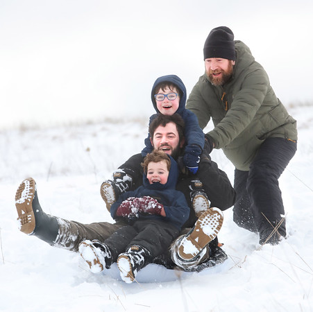MIKE SPRINGER/Staff photo<br /> Three generations of the Myers family -- grandpa Jacob, right, of Amesbury, his son Jacob, of Dover, New Hampshire, and his grandsons Jasper, 4, and Jace, 6 -- go sledding together Tuesday in the heavy snow at Woodsom Farm in Amesbury.