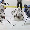 MIKE SPRINGER/Staff photo<br /> Newburyport's Jonathan Groth, left, clears the puck away from the goal as goalie Jackson Marshall and Cael Kohan of Triton look one during varsity hockey action Monday in Newburyport. Behind Groth is teammate Owen Spence.