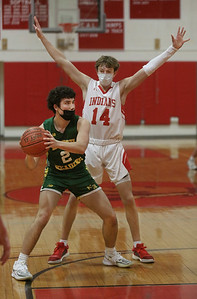 MIKE SPRINGER/Staff photo North Reading's John Jennings looks for someone to pass to while under defensive pressure from Matthew Welch of Amesbury during varsity basketball action Friday in Amesbury.