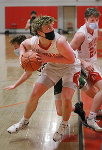 MIKE SPRINGER/Staff photo Amesbury's Kyle Donovan looks up at the basket after taking control of a rebound during varsity basketball action Friday against North Reading in Amesbury.
