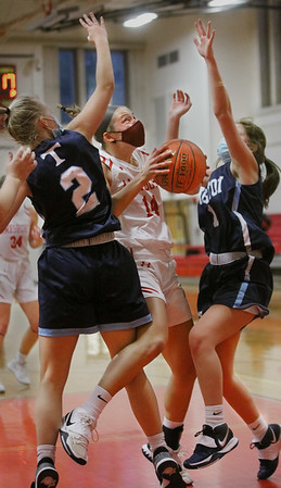 MIKE SPRINGER/Staff photo<br /> Amesbury's Alyssa Pettet, center, squeezes between Page Leavitt, left, and Molly Kimball of Triton as she goes up for a shot during varsity basketball action Wednesday in Amesbury.