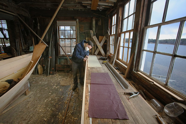 """MIKE SPRINGER/Staff photo<br /> Aaron Cross of Amesbury uses a plane to shape a """"sheer plank"""" for a Grand Banks dory, a type of small fishing boat that was used in the 19th Century, at Lowell's Boat Shop on Wednesday in Amesbury. Activity at the shop has slowed down due to Covid-19, but some apprentice boat-building programs, including one for high school students and another for 10 to 12 year olds, are still going on."""