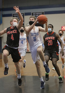 MIKE SPRINGER/Staff photo Triton's Kyle Odoy goes up for a shot against  Charlie Henderson, left, and Nikhil Walker of Ipswich during varsity basketball action Friday at Triton.