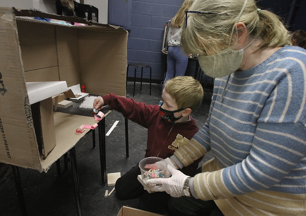 MIKE SPRINGER/Staff photo<br /> Tinkerhaus Director Mary McDonald helps five-year-old Jonas Pollard work on a doll house Thursday. The Tinkerhaus center was keeping children busy working on crafts between online class sessions.