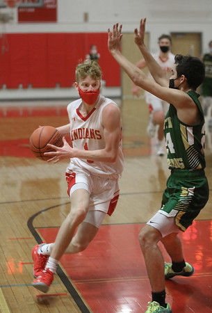 MIKE SPRINGER/Staff photo Amesbury's Camden Keliher  goes up for a shot against Cody Cannalonga of North Reading during varsity basketball action Friday in Amesbury.