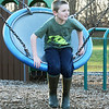 BRYAN EATON/Staff Photo. Declan Kenny, 9, sits on a giant swing at the Newbury Elementary School playground on Tuesday. He was in the afterschool Kid's Club which do different activities and went outside for the nice weather.
