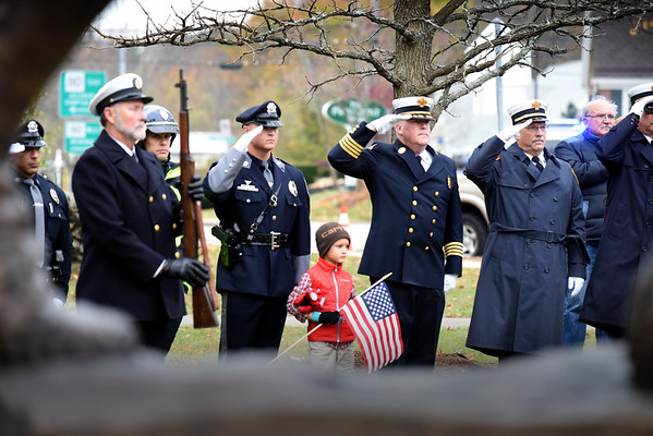BRYAN EATON/Staff Photo. Amesbury fire and Amesbury and state police members salute during the Star-Spangled Banner.