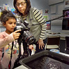 BRYAN EATON/Staff Photo. Photography instructor Kathy Milstein looks on as Jadalyn Aponte, 6, tries her hand at photographing drops of water with a flash mounted on the side at the Boys and Girls Club. Milstein teaches photo basics in the classes on Tuesday and Wednesdays and as the youngsters get more proficient, takes them on nearby field trips to photography scenery, still lifes, etc.