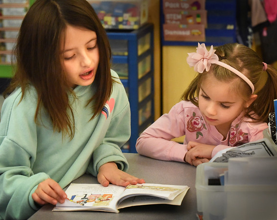 """BRYAN EATON/Staff Photo. Ruby Lawless, 8, left, reads """"Teach Us, Amelia Bedilia"""" to Lexi Alfano, 5, at the Bresnahan School in Newburyport on Friday. The third-graders get together once a week for Reading Buddies with the kindergartners which helps the younger students appreciate reading and gives the third-graders confidence and builds friendships."""
