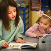 "BRYAN EATON/Staff Photo. Ruby Lawless, 8, left, reads ""Teach Us, Amelia Bedilia"" to Lexi Alfano, 5, at the Bresnahan School in Newburyport on Friday. The third-graders get together once a week for Reading Buddies with the kindergartners which helps the younger students appreciate reading and gives the third-graders confidence and builds friendships."