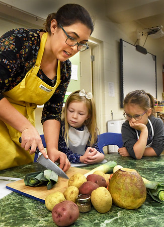"BRYAN EATON/Staff Photo. Children from Our Secret Garden, at Newbury's First Parish Church, are involved in a six-week long enrichment class called ""Food for the Soul"" taught by their teacher Kristine Soares. Felicity Fisher and Mariella Hull, both 5, watch as Soares cuts up a leek to be used in a potato leek soup the children are helping to prepare learning how simple ingredients can turn into something delicious while providing nourishment. Part of the lessons included the fact that not everyone can afford to buy these items on a regular basis and that there are people in their own neighborhoods who often go hungry. Before making the soup the children brought food items from home upstairs to the Newbury Community Food Pantry and helped sort them onto shelves."