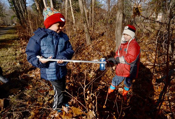 BRYAN EATON/Staff photo. Braedyn King, 7, left, and Damien Pearson, 9, of Salisbury pick up garbage on the Ghost Trail in Salisbury on Saturday morning. They were volunteering for the Coastal Trails Coalition fall cleanup. Volunteers also were on the Marsh Trail and the Riverwalk Trail in Amesbury.