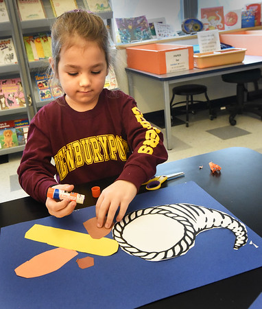 BRYAN EATON/Staff Photo. Wearing a Newburyport High football shirt, Annie Dupuis, 5, creates the elements of a curnucopia at the Bresnahan School. She was in Pam Jamison's art class where the kindergartners were learning about the symbol of harvest and plenty.