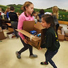 BRYAN EATON/Staff Photo. The Cashman School's fourth grade student council organized once again a Thanksgiving Food Drive which started just after Halloween. Monday was the day the Our Neighbors' Table sent the truck to be filled with the non-perishable items. Kylee Houle, 10, left, and Kaelyn Broderick, 9. carry a box filled with canned goods and pasta from the Amesbury school's hallway to the curbside.