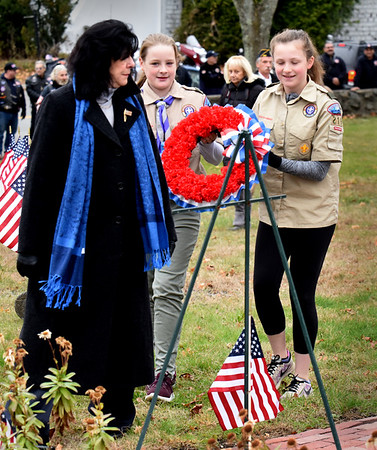 BRYAN EATON/Staff Photo. Newburyport Mayor Donna Holaday is assisted by Scout BSA Troop 219 of Newburyport members, Erin Casco, center, and Katie Conway as she places a wreath at the monument in the Veterans Cemetery.