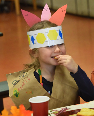 BRYAN EATON/Staff Photo. Tova Johnson, 5, munches on a cracker as her headband is a little too loose and kept covering her eyes. She was at the Friendship Feast that kindergartners celebrate every year at the Cashman School in Amesbury with a menu of crackers, cornbread, apple sauce and cheese. They learned the value of friendship, tied in with learning about Thanksgiving, and made friendship necklaces for fellow classmates after pulling names from a bucket.