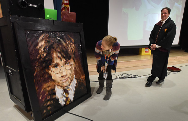 BRYAN EATON/Staff Photo. Pine Grove School art teacher Jen Dubis checks out a lego mural of Harry Potter that artist Rob Surrette, right, worked on last month with her students. Each student helped to make a part of the work, but didn't know what the creation would be until the unveiling this week.