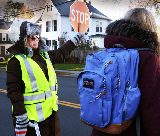 BRYAN EATON/Staff Photo. Newburyport Schools' crossing guard Corrie Parseghian is well-bundled up against Wednesday's cold and wind while tending to walkers on High and Johnson Streets. Cold is in the forecast again for today with a warmup Friday and then cold again for the weekend.