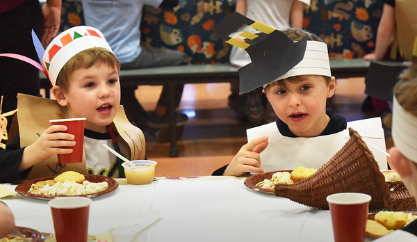 BRYAN EATON/Staff Photo. Ryan Baggeroer, 5, left, and Will Doyle, 6, chat with friends at the Friendship Feast that kindergartners celebrate every year at the Cashman School in Amesbury with a menu of crackers, cornbread, apple sauce and cheese. They learned the value of friendship, tied in with learning about Thanksgiving, and made friendship necklaces for fellow classmates after pulling names from a bucket.