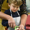 BRYAN EATON/Staff Photo. Soares helps Connor Mandeville, 3, peel a red potato for the soup.